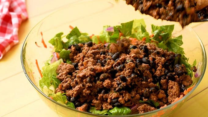 Adding taco seasoned beef to easy taco salad