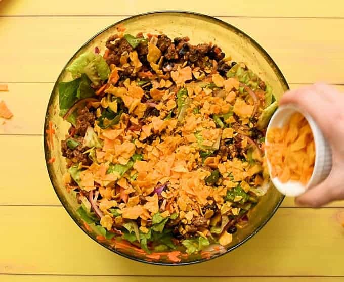 Adding crushed tortilla chips to the best taco salad