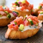 Greek Bruschetta Recipe with toast, creamy feta spread, and Greek seasoned toppings on a cutting board