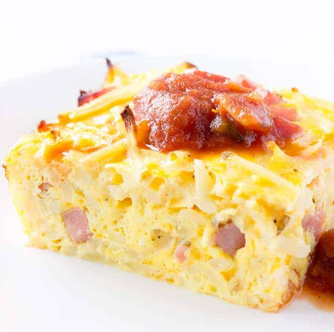 Slice of Hash Brown Breakfast Casserole with salsa on top