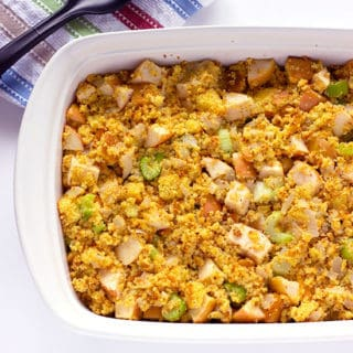 Large serving dish of corn bread stuffing with apples celery and onions