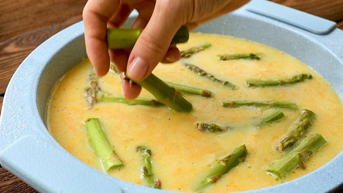 Adding chopped asparagus to a pie plate with ham and cheese quiche ingredients