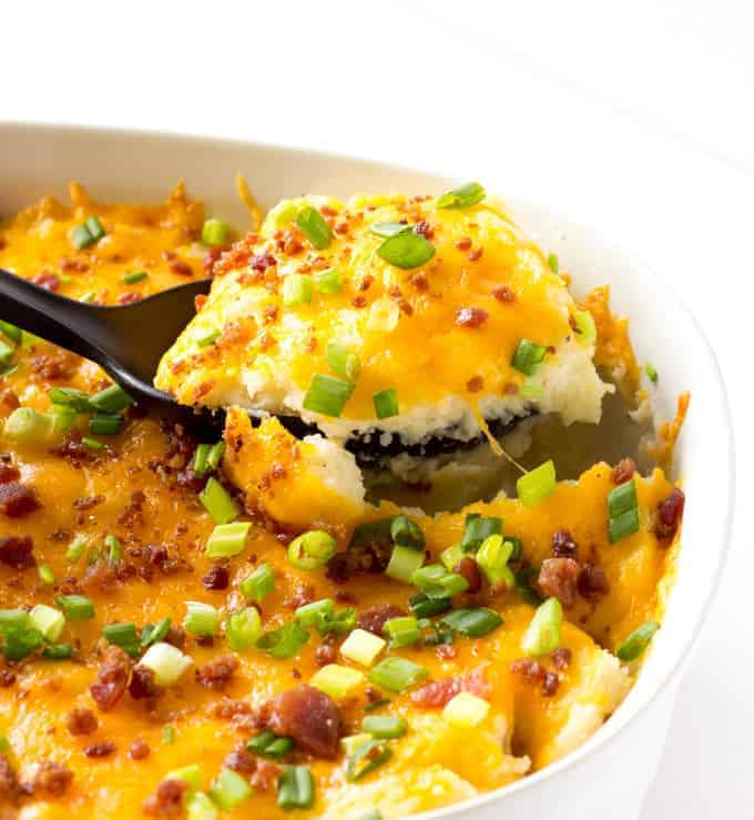 spoon scooping out cheesy mashed potato casserole