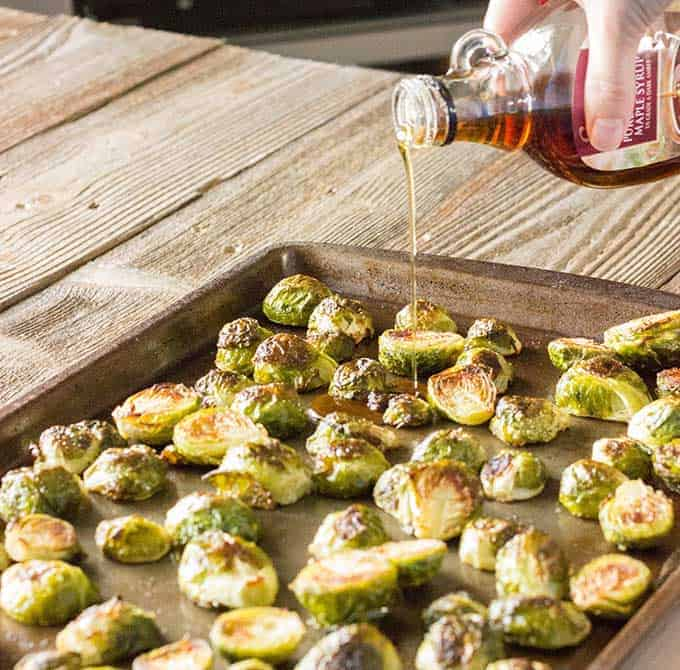 Maple syrup being poured over roasted brussels sprouts
