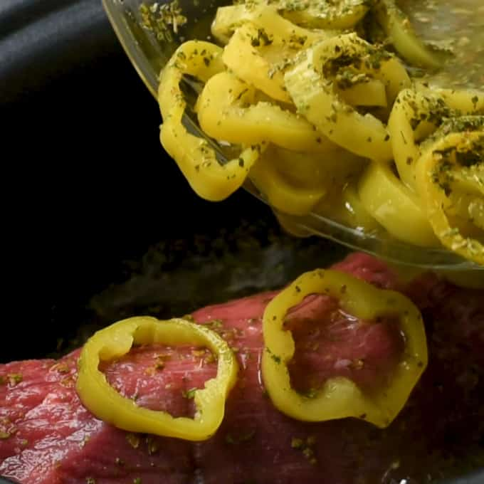 Pouring pepper rings and dressing mix over eye of round roast