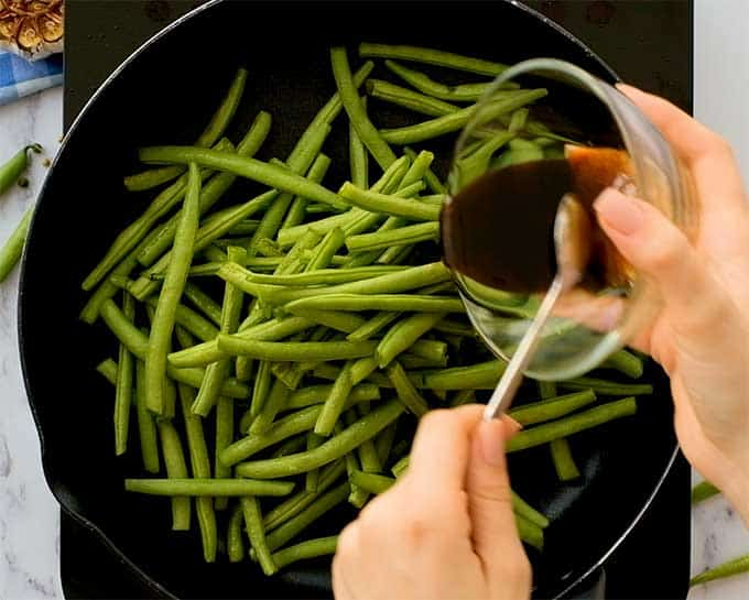 Fresh green beans in a large skillet with Asian sauce being poured over them