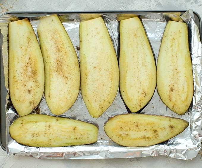 Sliced eggplant on a baking sheet for roasting