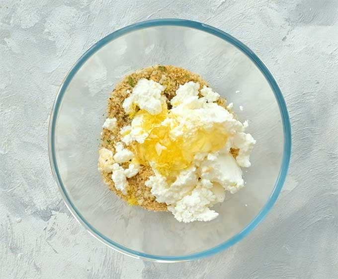 mixing bowl full of Italian seasoned breadcrumbs, ricotta cheese, honey, and lemon zest for stuffed eggplant