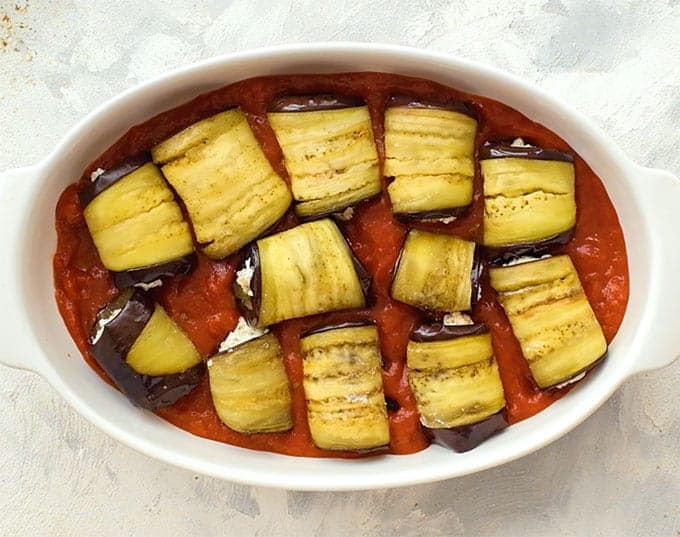 Sliced roasted eggplant rolled around ricotta in a baking dish with marinara sauce