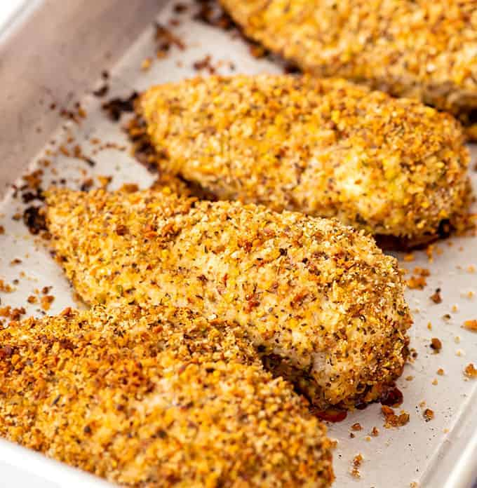 Baking dish full of cooked pistachio crusted chicken breasts