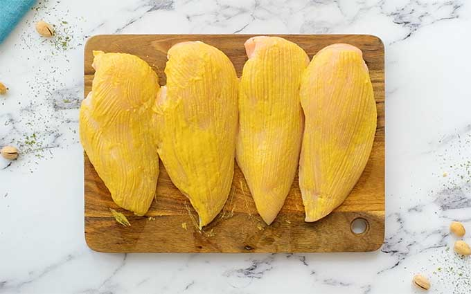 Four boneless skinless chicken breasts on a cutting board coated in honey mustard sauce