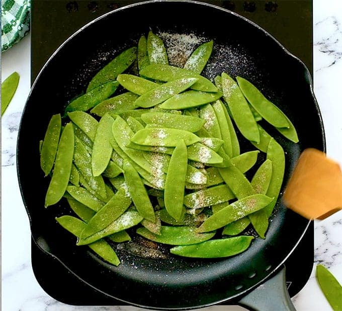 Sugar snap peas in a sautée pan with oil, salt, and pepper