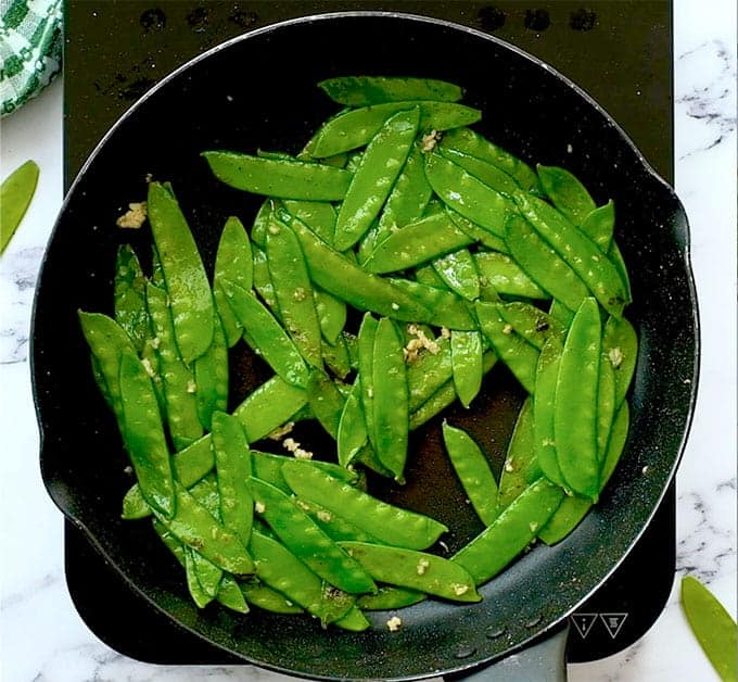 sautéed sugar snap peas with garlic in a skillet