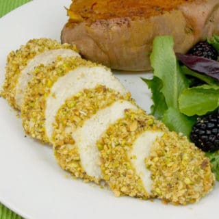Pistachio Crusted Chicken sliced on a plate with sides