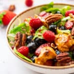Salad with chicken, berries, and poppyseed dressing in a bowl