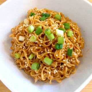Sesame Peanut Butter Noodles in a white bowl topped with sesame seeds and sliced green onions