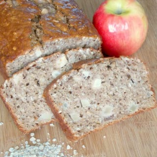 apple cinnamon oatmeal bread sliced on a cutting board with an apple and oats