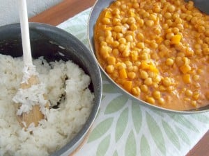 skillet full of coconut curry garbanzo beans next to a pot of cooked white rice