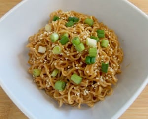 white bowl full of sesame peanut noodles topped with green onions