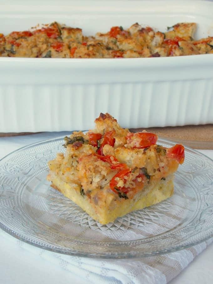 یک تکه پودینگ نان ریحان گوجه فرنگی روی یک بشقاب با یک ظرف پخت در پس زمینه