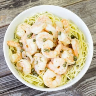 Shrimp Piccata over pasta in a white bowl