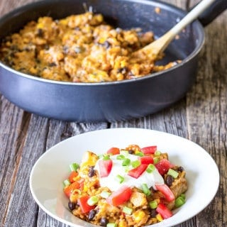 white bowl full of One Pot Chicken Enchilada Bowls with skillet in the background