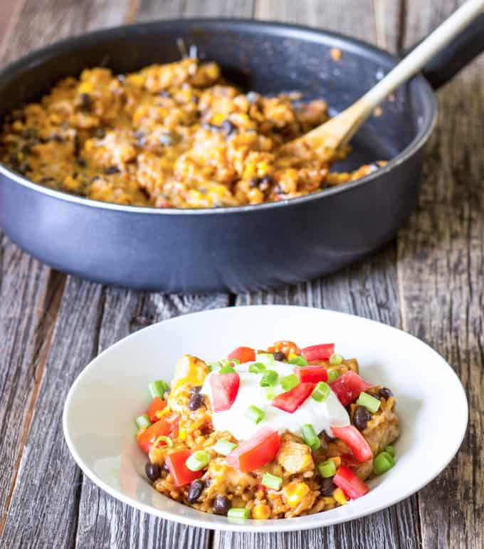 white bowl full of One Pot Wonder Chicken Enchilada Bowls with skillet in the background