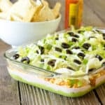 glass casserole dish full of 7 Layer Chicken Taco Dip