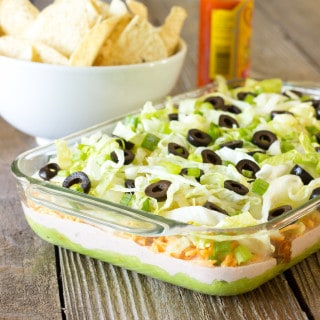 casserole dish full of 7 Layer Chicken Taco Dip with tortilla chips in the background