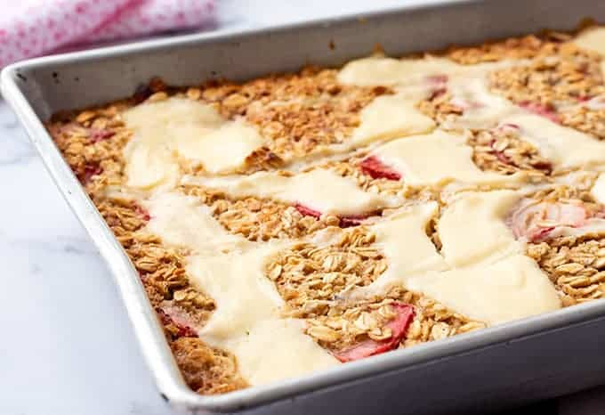 Baking dish full of strawberry baked oatmeal with a cream cheese swirl