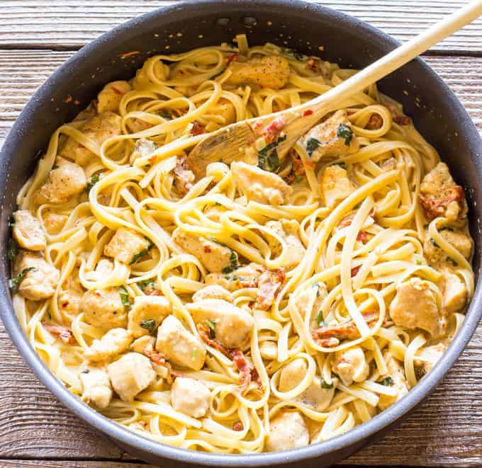skillet full of Chicken Fettuccini in Sun-Dried Tomato Basil Cream Sauce in a skillet