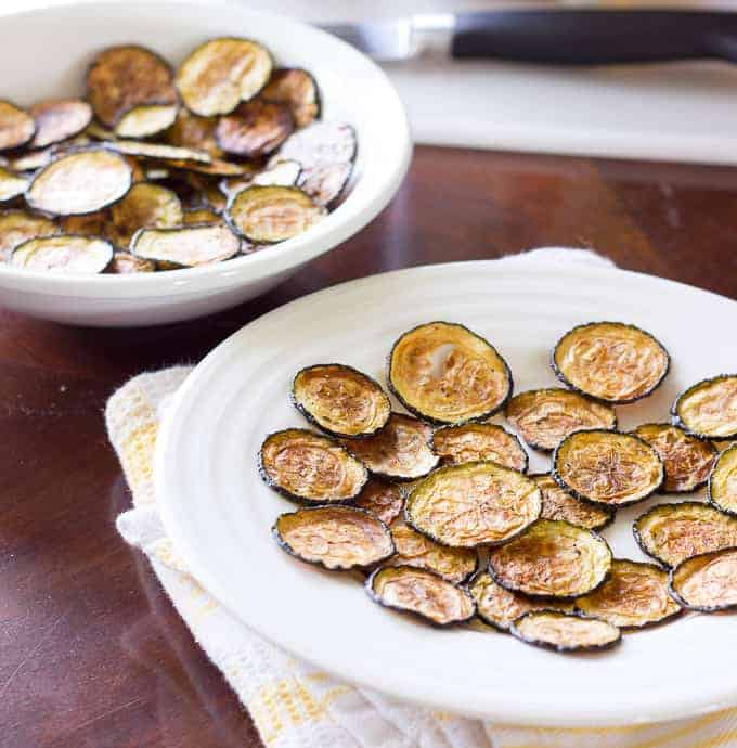 white plate and bowl full of Salt and Vinegar Zucchini Chips