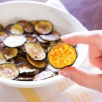 Salt and Vinegar Zucchini Chips in a white bowl and one being held up