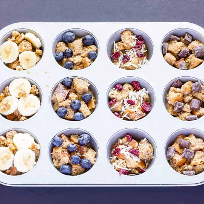 uncooked French Toast Cups with different Toppings in a muffin tin