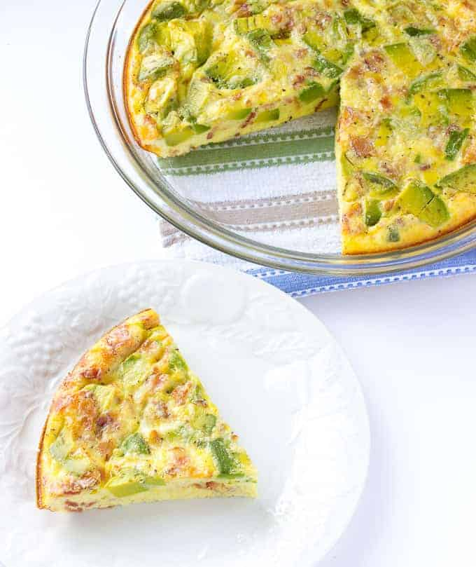 Avocado Bacon Crustless Quiche with one piece taken out and put on a white plate