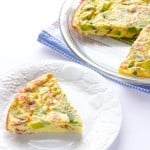 Avocado Bacon Crustless Quiche with one slice taken out on a white plate