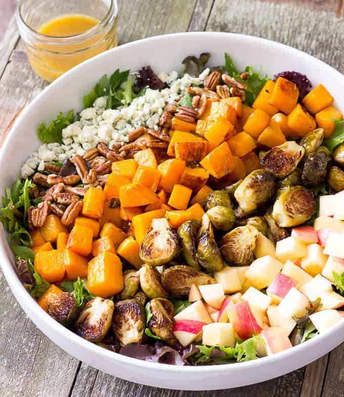white bowl full of Roasted Butternut Squash & Brussels Sprouts Harvest Salad with Maple Cider Vinaigrette