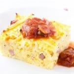 A piece of easy breakfast casserole on a white plate with some salsa