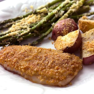 Parmesan crusted pork chops with roasted red potatoes and asparagus on a plate