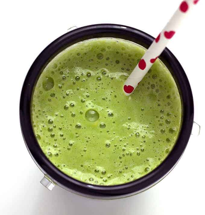 cup full of Tropical Green Smoothie with a straw