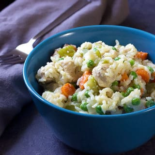 bowl of creamy chicken and rice with veggies and parmesan