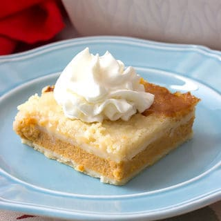 slice of Pumpkin Pie Cobbler with whipped cream on a blue plate with