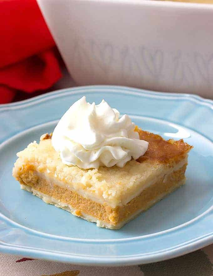 Pumpkin Pie Cobbler topped with whipped cream on a blue plate