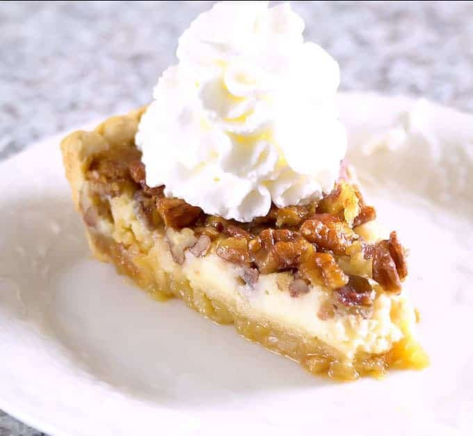Cheesecake Stuffed Pecan Pie topped with whipped cream on a white plate