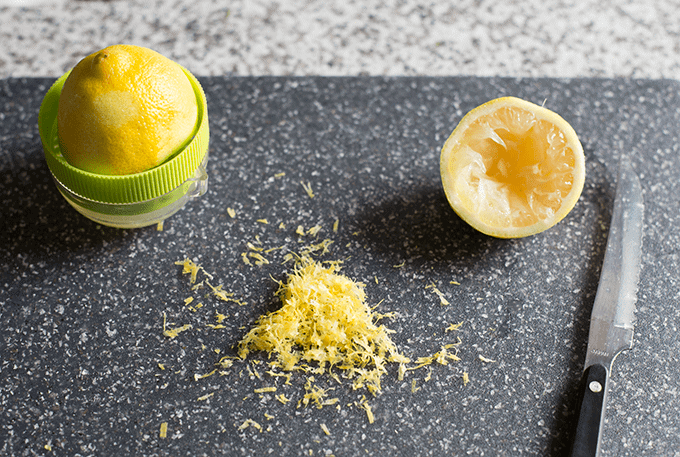 lemon zest, a cut lemon, and a lemon juicer on a dark grey cutting board
