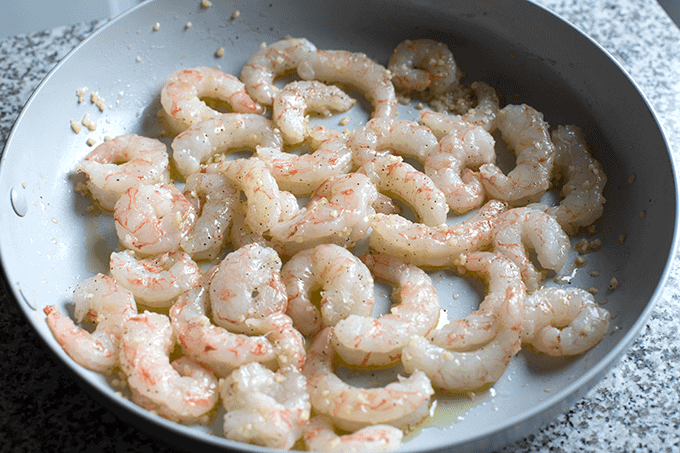 uncooked jumbo shrimp in a skillet with garlic and olive oil