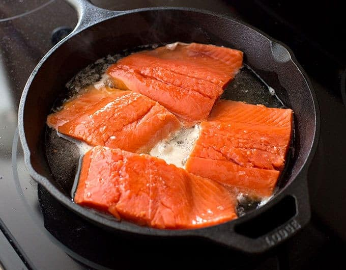 Salmon being cooked in a cast iron skillet