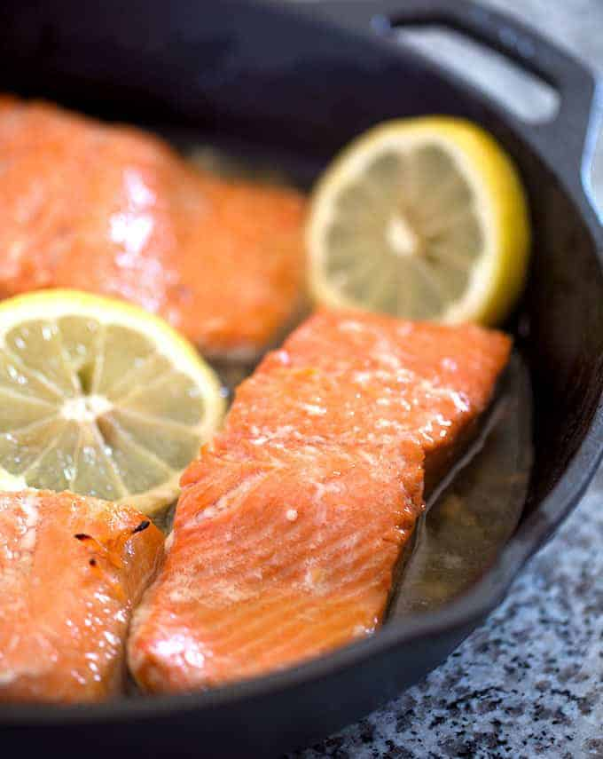 Cooked salmon in a cast iron skillet with lemon slices