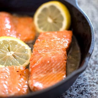 Cooked salmon in a cast iron skillet with honey and lemon slices