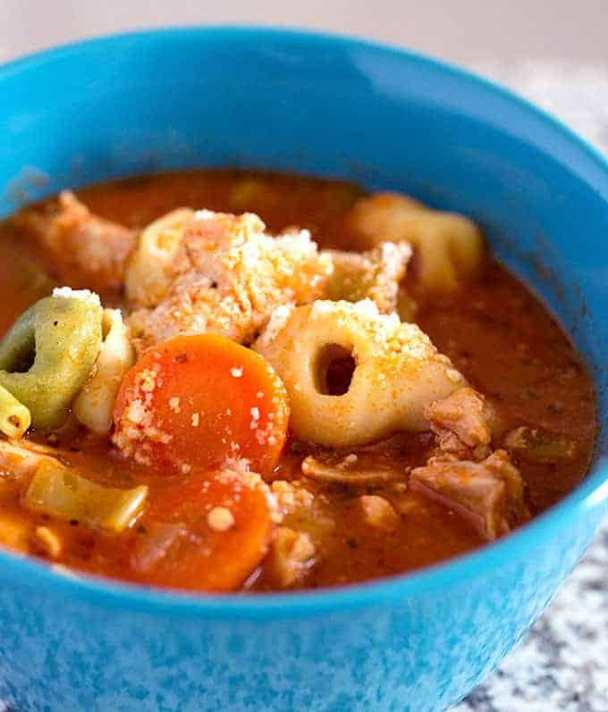 Crock Pot Italian Chicken Tortellini Soup recipe in a blue serving bowl